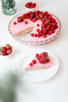 Fetta di cheesecake fatta in casa con lamponi freschi e foglie di menta su un piatto bianco sul tavolo. dessert estivo biologico sano