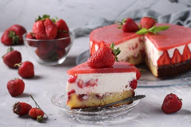 Torta di formaggio fatta in casa con fragole e gelatina sulla superficie grigia e fetta di torta su un piatto in primo piano