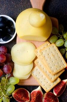 Pasta filata di formaggio fatta in casa, provolone su tavola rotonda in legno piatto sullo sfondo di legno.