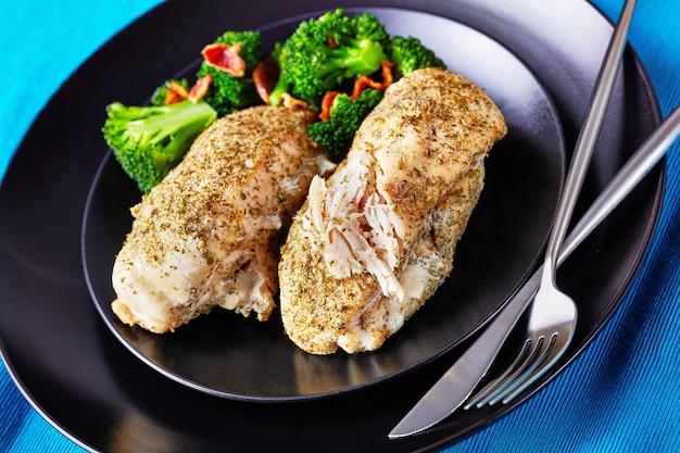 Filetto di pollo fatto in casa al forno con condimento ranch servito su un piatto nero con broccoli e pancetta con posate d'argento su uno sfondo di cemento scuro, orientamento orizzontale, primo piano