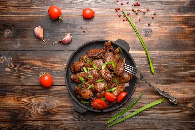Fegato di pollo fatto in casa fritto con salsa di soia, pomodori, cipolle e spezie. avvicinamento. messa a fuoco selettiva. cibo salutare