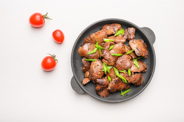 Fegato di pollo fatto in casa fritto con salsa di soia, pomodori, cipolle e spezie su sfondo chiaro.