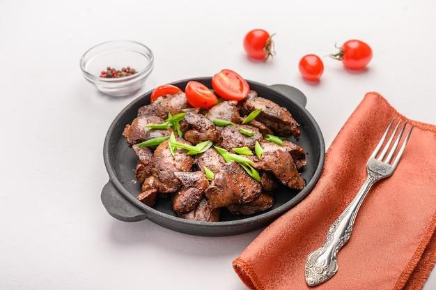 Fegato di pollo fatto in casa fritto con salsa di soia, pomodori, cipolle e spezie su tovagliolo di lino con forchetta. cibo salutare.