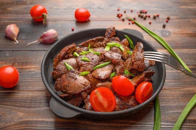 Fegato di pollo fatto in casa fritto con salsa di soia, pomodori, cipolle e spezie sulla tavola di legno. fetta di puntura in una forchetta. cibo salutare.
