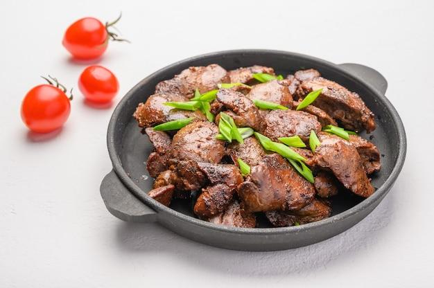 Fegato di pollo fatto in casa fritto con salsa di soia, pomodori, cipolle e spezie. Foto Premium
