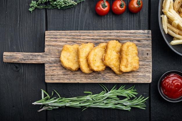 Pepite di pollo fatte in casa fritte sulla tavola di legno nera, vista dall'alto