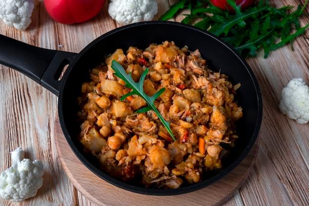 Spezzatino di pollo fatto in casa con verdure, patate, cipolla, carota, cavolfiore, pepe con salsa di pomodoro, aglio ed erbe aromatiche in una padella sul tavolo di legno. cibo rustico su fondo in legno