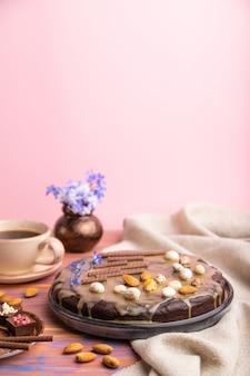 Torta brownie al cioccolato fatta in casa con crema al caramello e mandorle con una tazza di caffè su uno sfondo colorato e rosa. vista laterale, messa a fuoco selettiva, copia spazio.