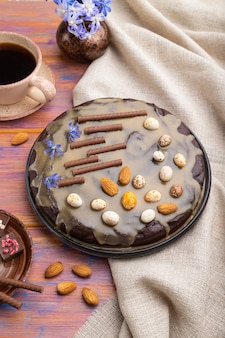 Torta brownie al cioccolato artigianale con crema al caramello e mandorle con tazza di caffè su uno sfondo di legno colorato e tessuto di lino.