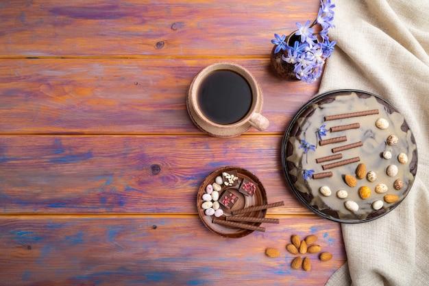 Torta brownie al cioccolato fatta in casa con crema al caramello e mandorle con una tazza di caffè su un fondo di legno colorato.