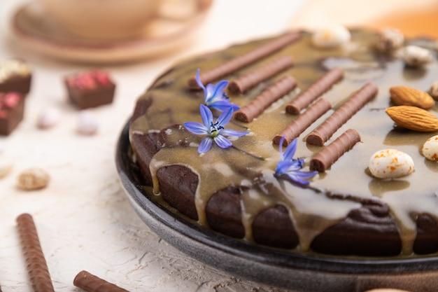 Torta brownie al cioccolato fatta in casa con crema al caramello e mandorle con una tazza di caffè su uno sfondo di cemento bianco.