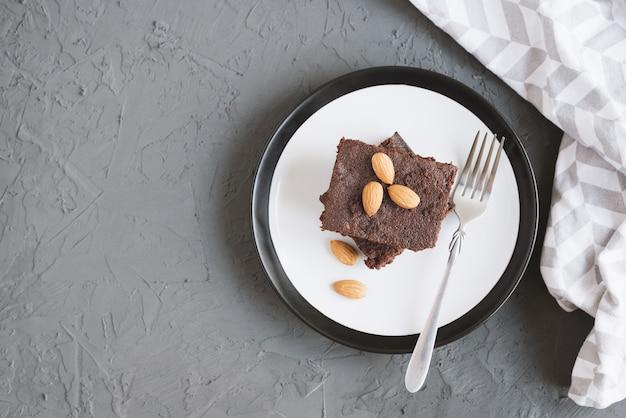 Brownie al cioccolato fatto in casa con mandorle e noci servito su un piatto con forchetta
