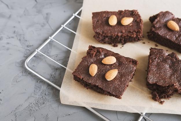 Brownies al cioccolato fatti in casa con mandorle e noci serviti su un vassoio con carta da forno