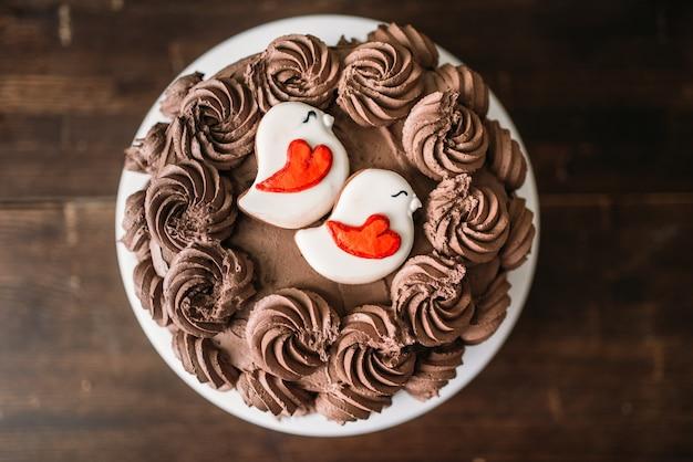 Torta al cioccolato artigianale, capolavoro culinario decorato con biscotti in smalto, vista dall'alto.