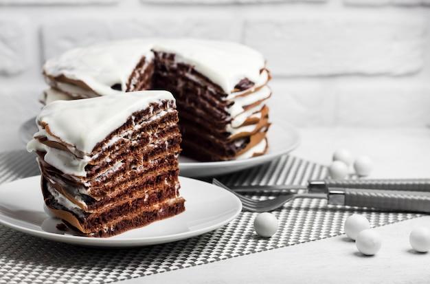 Torta al cioccolato fatta in casa con crema su piatti bianchi e posate su tavolo bianco e muro di mattoni bianchi