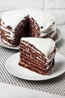 Torta al cioccolato fatta in casa con crema su piatti bianchi su tavolo bianco e muro di mattoni bianchi