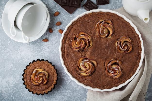 Torta al cioccolato artigianale con frangipane e fiori di melo su sfondo grigio chiaro di cemento o pietra