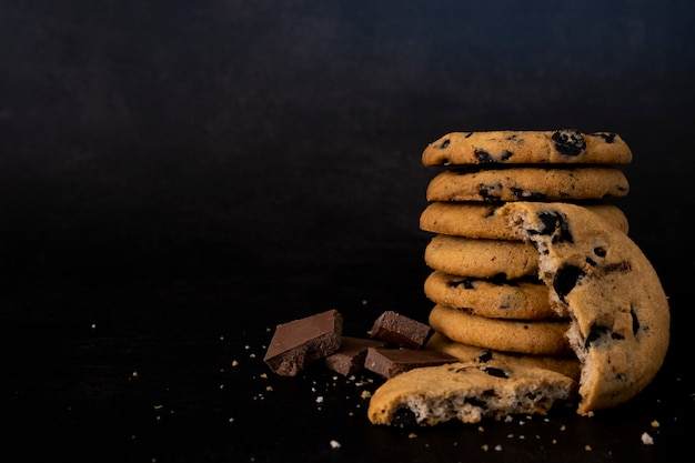 Biscotti fatti in casa con scaglie di cioccolato su una pila isolata su sfondo nero