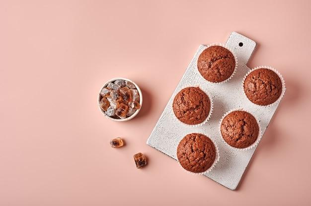 Cupcakes al cioccolato fatti in casa in carta da forno forme sul tagliere su sfondo rosa polveroso in alto