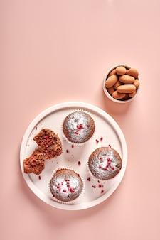 Cupcakes al cioccolato fatti in casa in forme di carta da forno e un pezzo di esso su un piatto leggero su rosa cipria