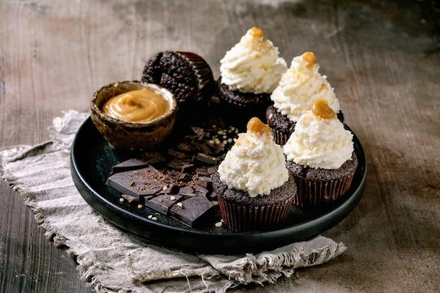 Muffin di cupcakes al cioccolato fatti in casa con crema di burro montata bianca e caramello salato, serviti con cioccolato fondente tritato su piastra in ceramica nera su sfondo texture di cemento.