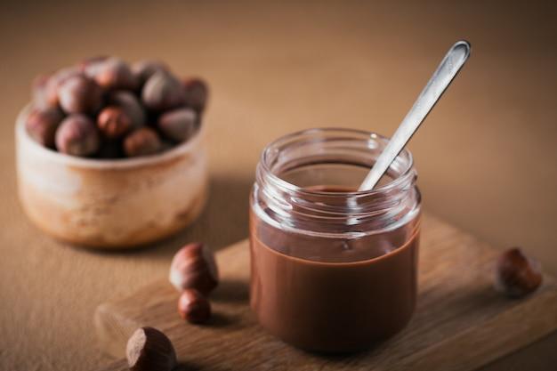 Latte di nocciole al cioccolato fatto in casa da spalmare su uno sfondo marrone