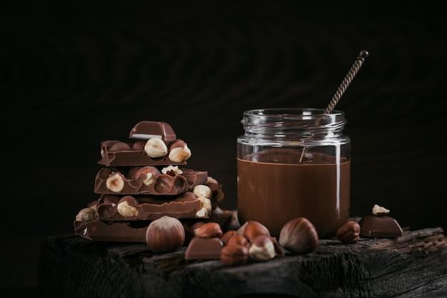 Latte di nocciola al cioccolato artigianale spalmato su uno sfondo scuro