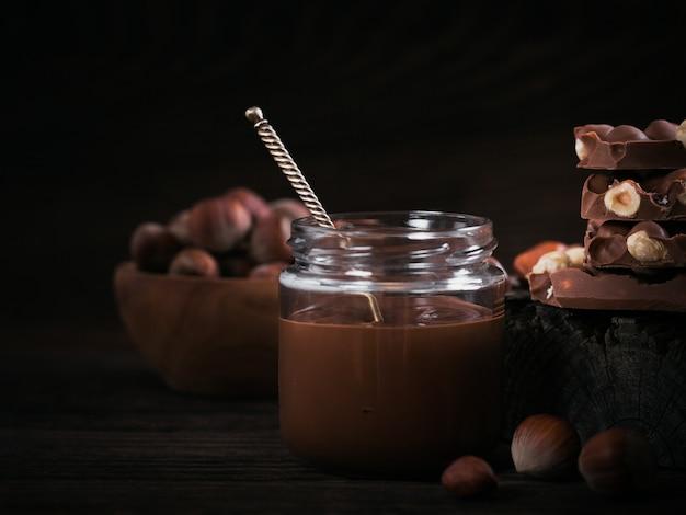 Latte di nocciole al cioccolato fatto in casa da spalmare su un barattolo di vetro su fondo di legno scuro