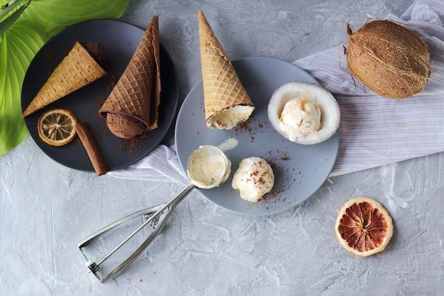 Gelato al cioccolato fatto in casa in coni di cialda noci di cocco su un tavolo luminoso prodotti per la cucina casalinga
