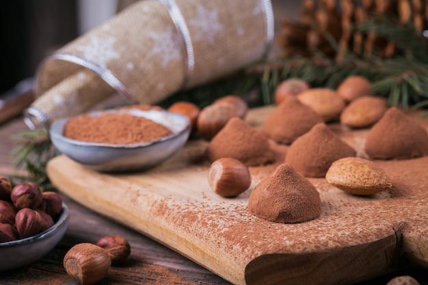 Tartufi di cioccolato fatti in casa, noci, mandorle e cacao in polvere su tagliere di legno. decorazione per le vacanze invernali.