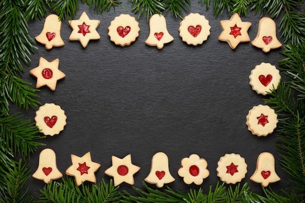 Biscotti fatti in casa di linzer di natale con marmellata di lamponi sul tavolo in ardesia con rami di pino