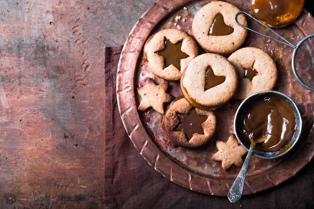 Biscotti casalinghi del caramello di forma della stella del nuovo anno di natale sopra fondo di legno. distesi piatti, spazio.