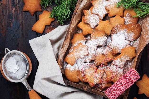 Biscotti fatti in casa di pan di zenzero a forma di stella di natale e capodanno nel piatto di ceramica sulla vecchia superficie d'epoca in legno
