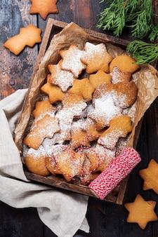 Biscotti fatti in casa di pan di zenzero a forma di stella di natale capodanno in una scatola di legno sulla superficie vintage in legno vecchio