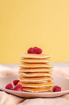 Frittelle americane classiche fatte in casa con lamponi freschi, more, miele e foglie di menta, su sfondo chiaro