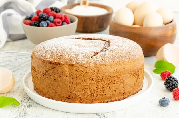 Classico pan di spagna alla vaniglia fatto in casa o biscotto cosparso di zucchero a velo e frutti di bosco freschi su un piatto bianco