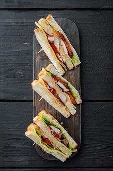 Club sandwich fatto in casa a base di tacchino, pancetta, prosciutto, pomodori, sul tavolo di legno nero, vista dall'alto