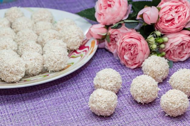 Caramelle di cocco fatte in casa su uno sfondo di fiori rosa. dolci per san valentino.