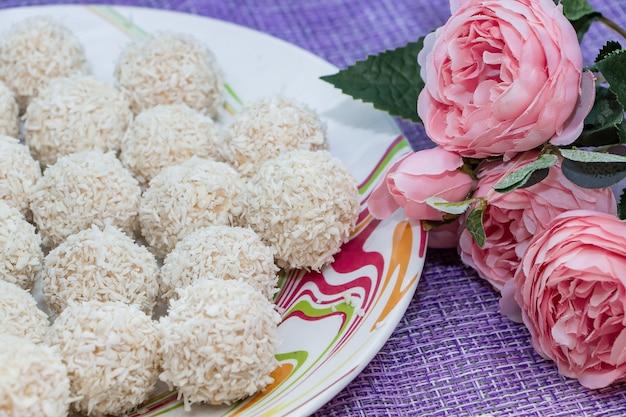 Caramelle al cocco fatte in casa e fiori rosa.