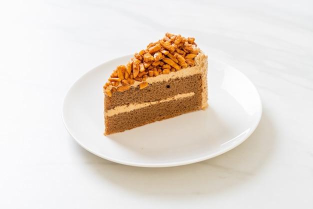 Fetta di torta di mandorle caffè fatto in casa sulla piastra bianca