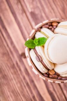 Amaretto o macaron al cioccolato fatti in casa con foglia di menta sulla parete in legno. vista dall'alto, copia dello spazio