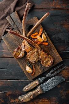 Costolette di agnello cucinate in casa con set di aglio e carote, sul tagliere, sul tavolo di legno scuro