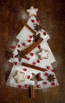 Biscotti fatti in casa piegati a forma di albero di natale con cannella su una teglia con zucchero a velo, vista dall'alto