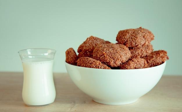 Biscotti fatti in casa e un bicchiere di latte sul tavolo.