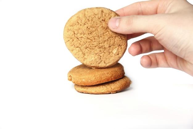 Biscotti fatti in casa in mano su un muro bianco