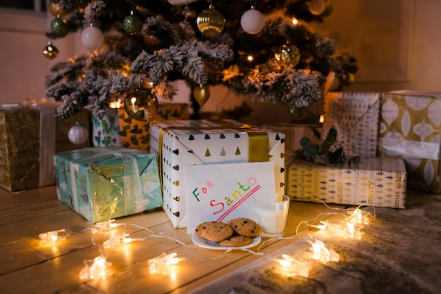 Biscotti fatti in casa e latte con nota alla vigilia di natale sotto l'albero con luci