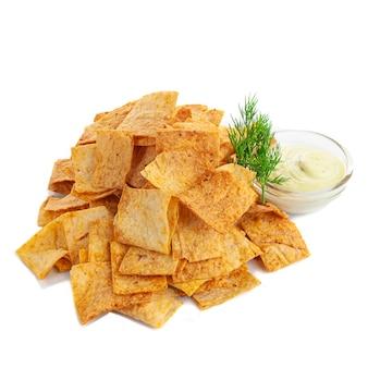 Chips di nachos di farina di mais fatti in casa con paprika. con salsa all'aglio ed erbe aromatiche. spuntino alla birra. sfondo bianco. isolato. avvicinamento.