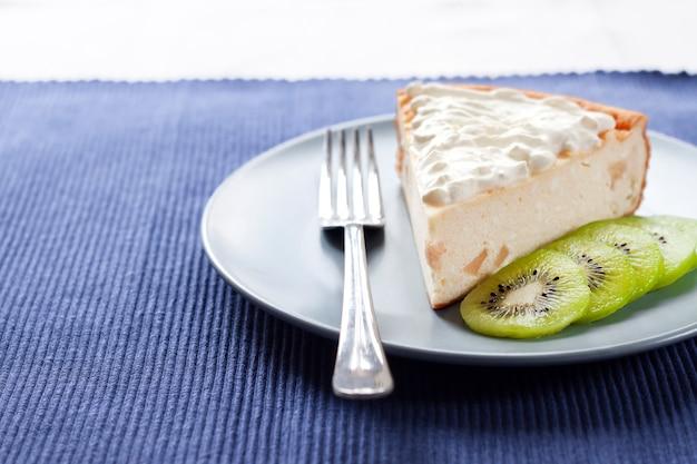 Torta di ricotta fatta in casa con kiwi e crema su un piatto.