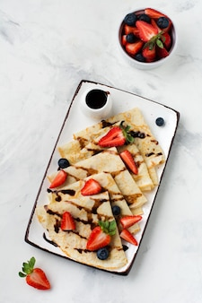 Frittelle di crepes fatte in casa con salsa al cioccolato, fragole fresche e miele per la colazione in un bellissimo piatto di ceramica bianca. spazio per testo o ricetta. vista dall'alto