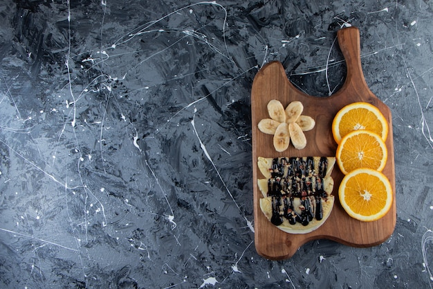 Crepes fatte in casa con cioccolato, banana a fette e arancia su tavola di legno.
